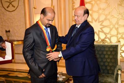 الرئيس هادي يمنح الشهيد اللواء اليافعي وسام الشجاعة أثناء إستقباله لنجله ( صوره)